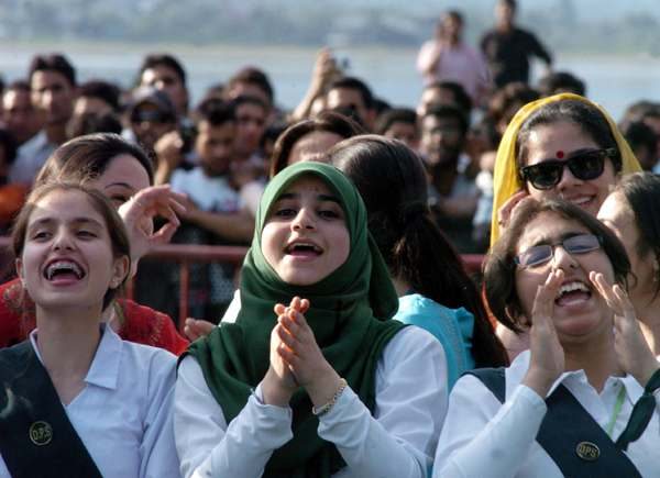 """Kashmiri Muslim girls enjoy the performance of Pakistan's top rock band """"Junoon"""" during the biggest musical event in decades amid opposition by rebels in Srinagar on May 25, 2008.   Thousands of violence-weary Kashmiris in the Indian-administered region danced and cheered during a rare performance by a top Pakistani rock band, the biggest musical event in decades.         AFP PHOTO/Tauseef MUSTAFA"""